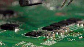 Desolder del microprocesador minúsculo del circuito integrado de la placa de circuito impresa que usa la estación que suelda del  almacen de metraje de vídeo