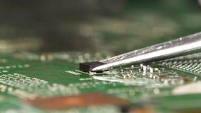 Desolder del pequeño microchip electrónico usando la estación que suelda del aire caliente y de pinzas de la placa de circuito almacen de video