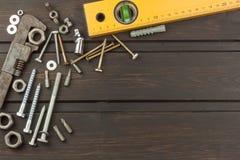 Desorden en la herramienta Preparación para el tratamiento casero Diversos herramientas, tornillos y nueces en un fondo de madera Foto de archivo libre de regalías