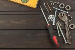 Desorden en la herramienta Preparación para el tratamiento casero Diversos herramientas, tornillos y nueces en un fondo de madera Foto de archivo