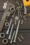 Desorden en la herramienta Preparación para el tratamiento casero Diversos herramientas, tornillos y nueces en un fondo de madera Imágenes de archivo libres de regalías