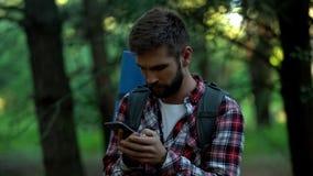 Desorienterad campare som söker för översikt, i smartphone, geocaching och att orientera arkivfoto