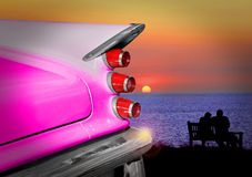 Desoto romance. Photo of an american classic vintage pink desoto car with romantic couple watching the sunset Stock Image