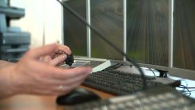 Despachador del servicio del camino en el centro de emergencia con los sistemas de vigilancia video externos de los monitores almacen de video