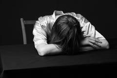 despair Женщина лежит на таблице, голове на руках стоковые фотографии rf