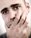 Despair. Young man holding his hand on his mouth as an act of depression Stock Photography