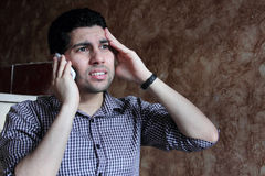Despair of arab egyptian businessman with headache talking with phone  Stock Photo