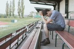 Despair and depressed man is sitting in stadium. Solitary and loneliness concept Stock Image