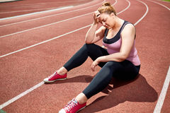Despair. Exhausted and desperate plump woman sitting on stadium racetrack Royalty Free Stock Images