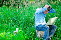 Young man outdoors with a cup and laptop Royalty Free Stock Images