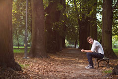 Despair man in the park. Lonely sad and despair man in the park on dark background. Earth is dying - ecology concept Stock Images