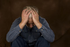 In Despair. A mature gray haired man in deep despair Stock Image