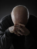 Despair of maturity. Senior bald man on dark background stock photos