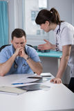 Despair medic sitting at the desk Stock Photography