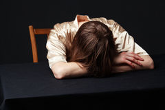 Despair. Woman is lying on the table, head on the hands. Face is hidden by the hair, gray backgroud Royalty Free Stock Image