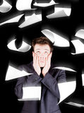 Despaired businessman with paperwork falling everywhere Royalty Free Stock Photo