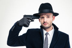 Despaired man in hat put gun to his temple Stock Photo