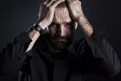 Despaired man looking worried with hands at forehead. Desperate frowning man looking miserable, on black background royalty free stock image
