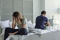 Despaired a marié des couples est sur le lit Image stock