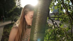 Despaired woman leaning her head on tree trunk stock footage