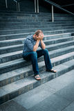 Despaired young man covering his face with hands sitting on stairs Royalty Free Stock Photos