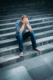 Despaired young man covering his face with hands sitting on stairs. Outdoor portrait of despaired young man covering his face with hands sitting on stairs royalty free stock photo