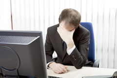 Despairing businessman at his desk Royalty Free Stock Photos