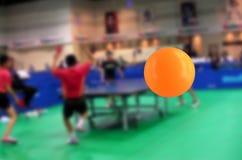 Despedir la bola de los tenis de mesa en el gimnasio Fotos de archivo