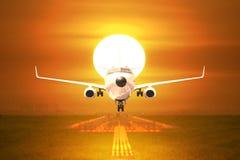 Despegue de los aviones de pasajero de la vista delantera en pista en puesta del sol Fotografía de archivo libre de regalías