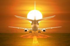 Despegue de los aviones de pasajero de la vista posterior en pista en puesta del sol Foto de archivo