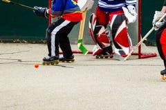 Despegue en tiempo mínimo de los jugadores de hockey delante de la meta Imagen de archivo libre de regalías