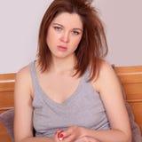 Desperacka chora kobieta z czerwonym nosa obsiadaniem na łóżkowych mienie pigułkach Zdjęcia Stock