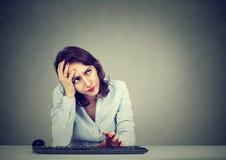 Desperacka kobieta próbuje notować w jej komputer zapominał hasło obraz royalty free