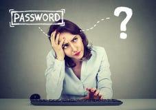 Desperacka kobieta próbuje notować w jej komputer zapominał hasło zdjęcia stock