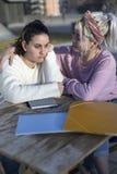 Desperacka studencka kobieta dostaje poparcie od jej najlepszego przyjaciela siedzi outdoors zdjęcie stock