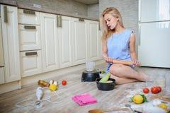 desperacki gospodyni domowej lying on the beach na podłoga w jej kuchni Obraz Royalty Free