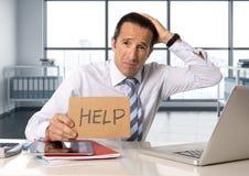 Desperat hög affärsman i krisen som arbetar på datorbärbara datorn på kontorsskrivbordet i spänning under tryck arkivfoton