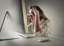 Desperat kvinna framme av en dator Arkivfoto