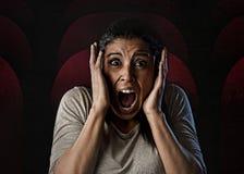 Desperat kvinna och förskräckt som terroriseras på filmen för fasa för biokorridor den hållande ögonen på Arkivbilder