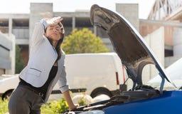 Desperat kvinna och hennes brutna bil Arkivfoton