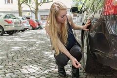 Desperat kvinna som kontrollerar skadan till hennes bil Royaltyfri Bild