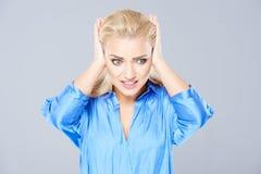 Desperat kvinna som rymmer hennes händer till hennes öron Arkivfoto