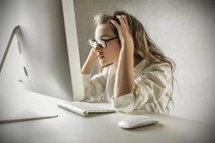 Desperat kvinna som ser hennes dator Royaltyfri Foto