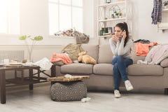 Desperat kvinnasammanträde på soffan i smutsigt rum arkivfoto