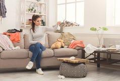 Desperat kvinnasammanträde på soffan i smutsigt rum arkivbilder
