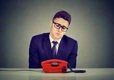 Desperat ledsen ung affärsman som väntar på någon att kalla honom arkivfoton