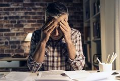 Desperat man som hemma kontrollerar hans inhemska räkningar royaltyfria foton