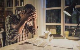 Desperat man som hemma kontrollerar hans inhemska räkningar fotografering för bildbyråer