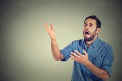 Desperat man som skriker att fråga för hjälp Arkivfoton
