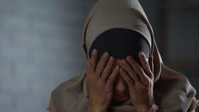 Desperat muslim gråta för kvinna som täcker framsidan med händer, familjproblem, skam stock video